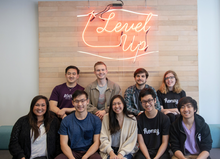 Interns posing with Level Up neon sign